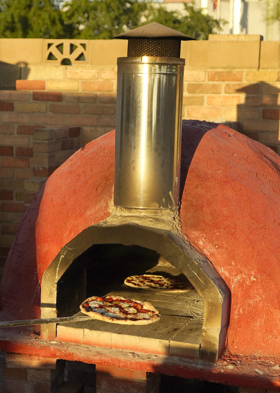 Chef Jose Hernandez checks on several pizzas in a clay oven in a makeshift backyard pizza kitchen on April 3, 2021, in Scottsdale, Ariz. Beaten down by the pandemic, some laid-off or idle restaurant workers have pivoted to dishing out food from home. (AP Photo/Ross D. Franklin)