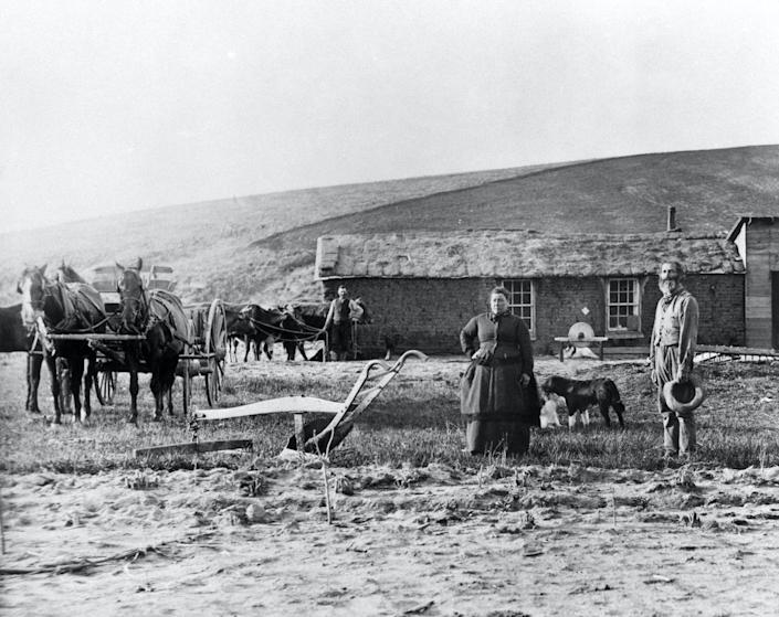 Men, a woman and some horses stand outside a sod home.