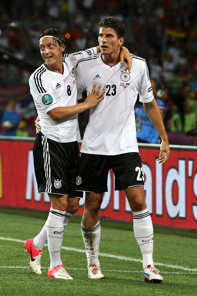 KHARKOV, UKRAINE - JUNE 13: Mario Gomez of Germany celebrates scoring their second goal with Mesut Ozil of Germany during the UEFA EURO 2012 group B match between Netherlands and Germany at Metalist Stadium on June 13, 2012 in Kharkov, Ukraine. (Photo by Ian Walton/Getty Images)