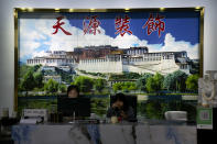 Workers sit beneath a large mural of the Potala Palace as they work at a logistics center in Nyingchi in western China's Tibet Autonomous Region, as seen during a rare government-led tour of the region for foreign journalists, Thursday, June 3, 2021. Long defined by its Buddhist culture, Tibet is facing a push for assimilation and political orthodoxy under China's ruling Communist Party. (AP Photo/Mark Schiefelbein)