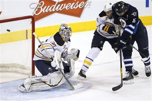 Winnipeg Jets' Andrew Ladd (16) and Buffalo Sabres' Mike Weber (6) fight for position as the shot flies past Sabres goaltender Ryan Miller (30) during first-period NHL hockey game action in Winnipeg, Manitoba, Thursday, Jan. 19, 2012. (AP Photo/The Canadian Press, John Woods)