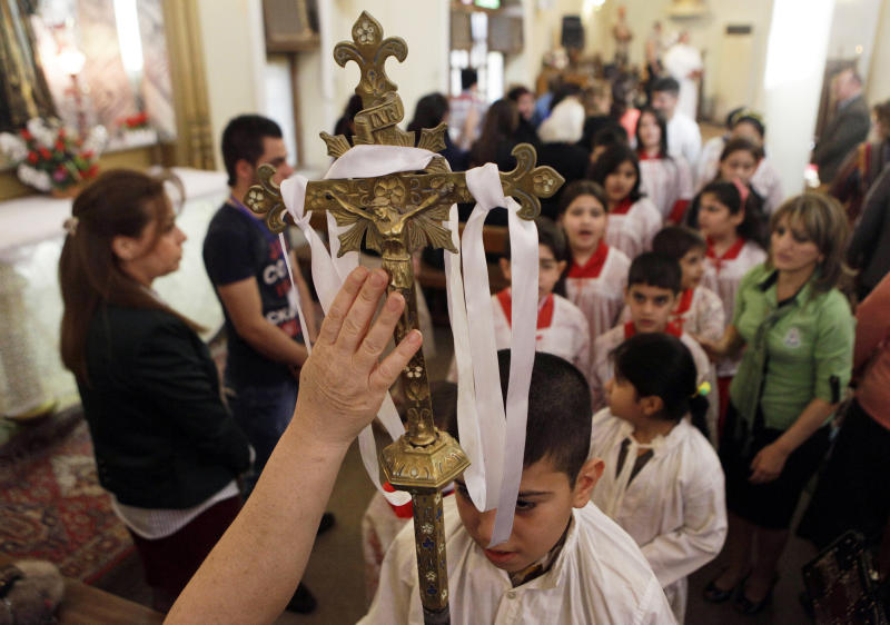 A worshipper reaches to touch a crucifix during Easter mass at Virgin Mary Chaldean Church in Baghdad, Iraq, Sunday, March 31, 2013. The Chaldean Church is an Eastern Rite church affiliated with the Roman Catholic Church. (AP Photo/ Khalid Mohammed)