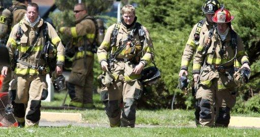 Firefighters exit the apartment of the James Holmes