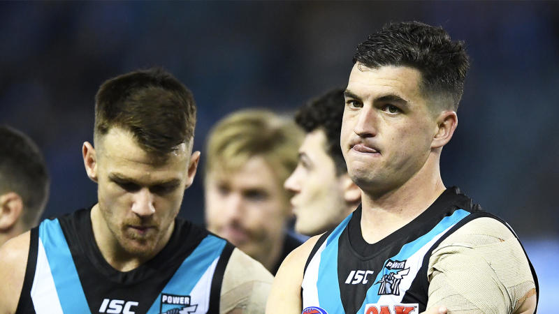 Tom Rockliff (pictured right) and his Power team mates look dejected.