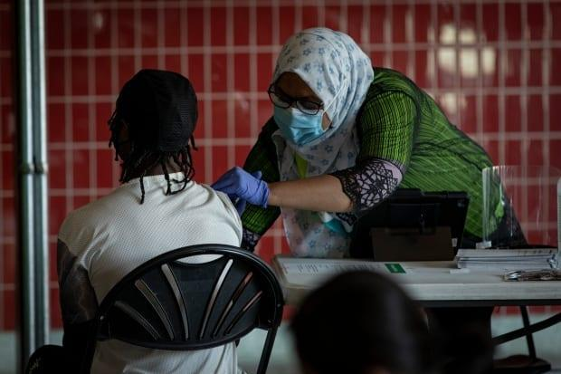A health care provider with East Toronto Health Partners administers a COVID-19 vaccine dose at a pop-up clinic in Victoria Park station in Toronto on Aug. 24, 2021. (Evan Mitsui/CBC - image credit)