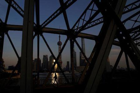 A man walks on a bridge in front of the financial district of Pudong in Shanghai