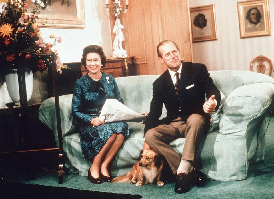 <p>The Queen and the Duke of Edinburgh relax with their corgis and a newspaper at Balmoral Castle in 1974.<br></p>