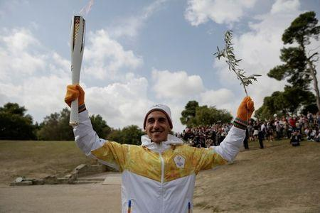 Olympics - Dress Rehearsal - Lighting Ceremony of the Olympic Flame Pyeongchang 2018 - Ancient Olympia, Olympia, Greece - October 23, 2017 First torchbearer Greek cross country skiing athlete Apostolos Aggelis holds the Olympic Flame and an olive branch during the dress rehearsal for the Olympic flame lighting ceremony for the Pyeongchang 2018 Winter Olympic Games at the site of ancient Olympia in Greece REUTERS/Alkis Konstantinidis