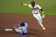 San Diego Padres shortstop Fernando Tatis Jr., right, goes over the top of Los Angeles Dodgers' Max Muncy, as Muncy slides in safely to second base during the 12th inning of a baseball game Friday, April 16, 2021, in San Diego. Los Angeles Dodgers' Chris Taylor grounded into a fielders choice, and Tatis picked up a fielding error on the play. (AP Photo/Gregory Bull)