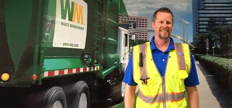 Waste Management employee stands by a garbage truck.