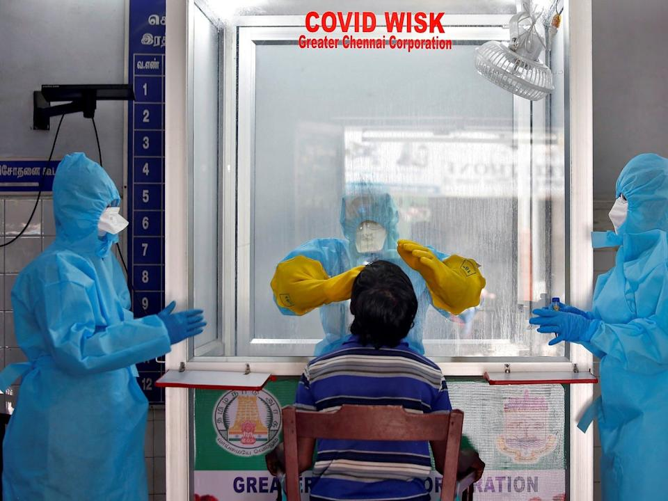 A doctor in a protective chamber takes a swab from a man to test for COVID-19 at a newly installed Walk-In Sample Kiosk (WISK) in a government-run hospital in Chennai, India, on April 13, 2020.