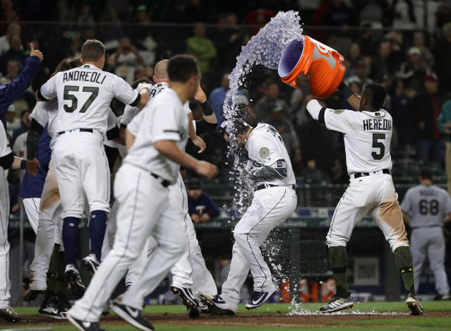 Seattle Mariners Mike Zunino, second from right, is doused with sports drink by teammate Guillermo Heredia, right, after Zunino hit a walk-off solo home run against the Minnesota Twins during the 12th inning of a baseball game, Saturday, May 26, 2018, in Seattle. The Mariners won 4-3. (AP Photo/Ted S. Warren)