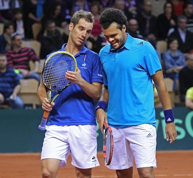 French players Jo-Wilfried Tsonga and Richard Gasquet, left, talk during their doubles match against Australian players Lleyton Hewitt and Chris Guccione in the first round of the Davis Cup between France and Australia, in La Roche sur Yon, western France, Saturday Feb. 1, 2014. (AP Photo/Remy de la Mauviniere)