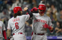 Cincinnati Reds' Jonathan India, left, congratulates Tyler Stephenson as he crosses home plate after hitting a two-run home run off Colorado Rockies relief pitcher Lucas Gilbreath during the eighth inning of a baseball game Thursday, May 13, 2021, in Denver. (AP Photo/David Zalubowski)