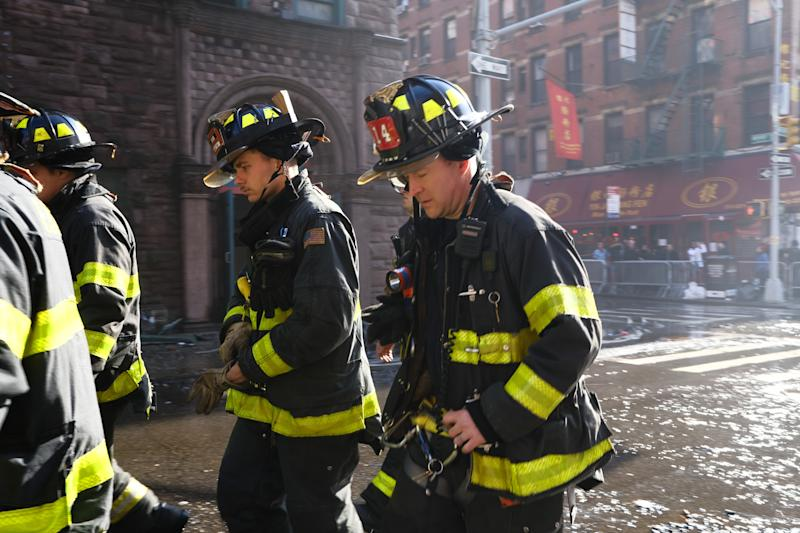 NEW YORK, NEW YORK - JANUARY 24: Firefighters walk at the scene of fire in Chinatown on January 24, 2020 in New York City. The fire, which is under investigation, severely damaged a historic building that has been home to a senior center and other nonprofits for decades and injured nearly a dozen people. Chinatown is preparing for Lunar New Year events tomorrow, which marks the start of the year of the rat. (Photo by Spencer Platt/Getty Images)