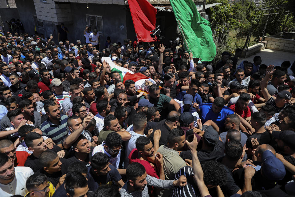 Palestinian mourners carry the body of Obaida Jawabreh, who was killed in clashes with Israeli forces, during his funeral in the West Bank refugee camp of Al-Arrub, Tuesday, May 18, 2021. (AP Photo/Mahmoud Illean)