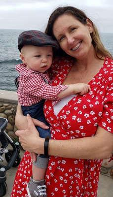 Raquel Wilkins wearing a red dress holding her son Denzel wearing a checked red shirt and a hat.