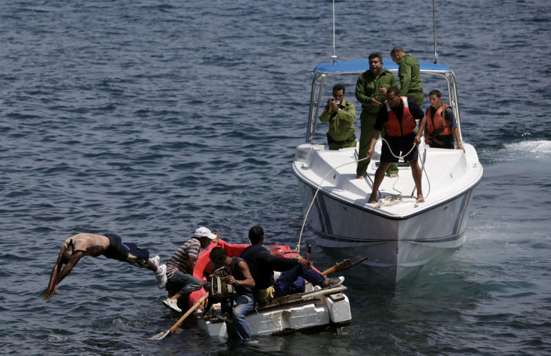 FILE - In this June 4, 2009 file photo, Cuban coast guards, right, stop seven men trying to migrate illegally to the U.S. on a foam raft near Havana's Malecon. No one was arrested, according to police. The United States and Cuba have agreed to resume bilateral talks on migration issues next month, a State Department official said Wednesday, June 19, 2013, the latest evidence of a thaw in chilly relations between the Cold War enemies. (AP Photo/Javier Galeano, File)