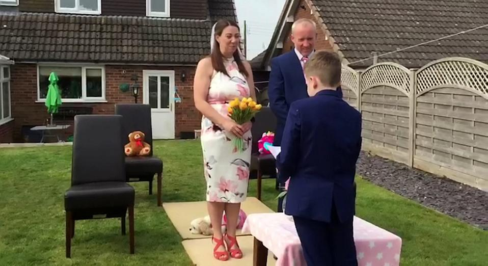 A couple who were forced to cancel their wedding have tied the knot in a surprise garden ceremony thrown by their kids (SWNS)