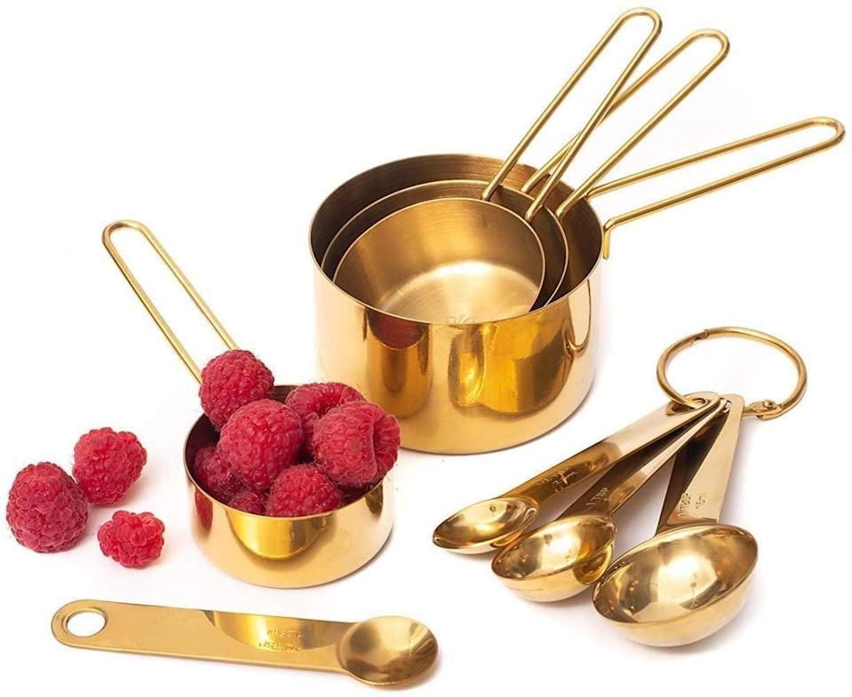 <p>You can't go wrong with this glistening <span>Modern Stainless Steel Measuring Cups and Spoons Set, Gold</span> ($23).</p>