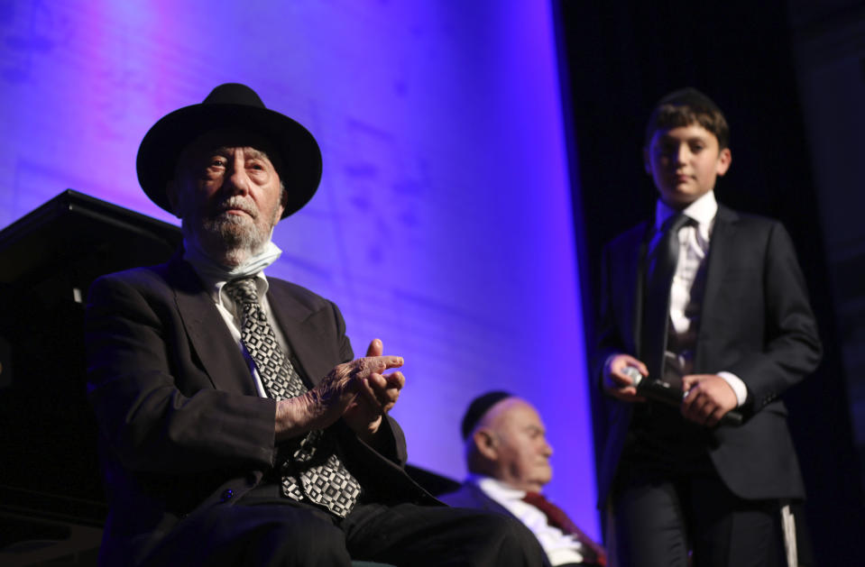 Aharon Wolf, 89, left, and David Einhorn, 95, center, sit on stage while Orthodox Jewish singer Yaakov Shwekey and young talent Nz Zlotowitz, right, perform a concert for them and other Holocaust survivors on Monday, June 14, 2021, at the Yeshivah of Flatbush theater at Joel Braverman High School in the Brooklyn borough of New York. It was the first large gathering for New York-area Holocaust survivors after more than a year of isolation due to the coronavirus pandemic. (AP Photo/Jessie Wardarski)