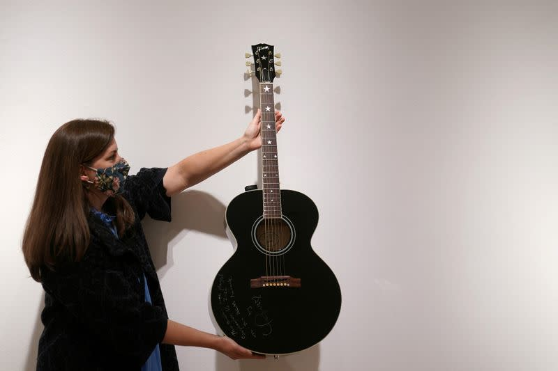 An employee of Christie's auction house holds a guitar used by singer Taylor Swift in New York