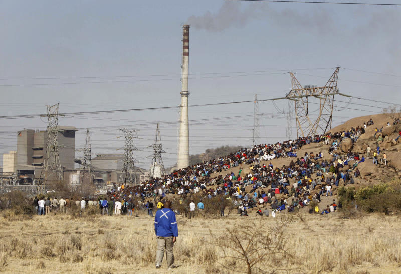 Striking mineworkers sit on a rocky outcropping near their shuttered platinum mine, Lonmin Platinum Mine near Rustenburg, South Africa, Tuesday, Aug. 14, 2012. The unrest over pay and dueling unions has killed at least 10 people and represents a sign of the unrest gripping South Africa's mining industry. Barnard O. Mokwena, an execute vice president for Lonmin, said the company continued to meet with the police regarding the unrest. On Tuesday, operations appeared at a standstill at a facility that represents 96 per cent of all production for the world's third largest platinum producer. (AP Photo/Denis Farrell)