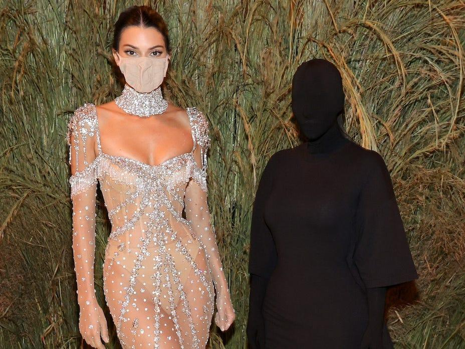 Kendall Jenner, wearing an ornate dress and facemask, stands next to Kim Kardashian, completely covered in black, at the Met Gala 2021