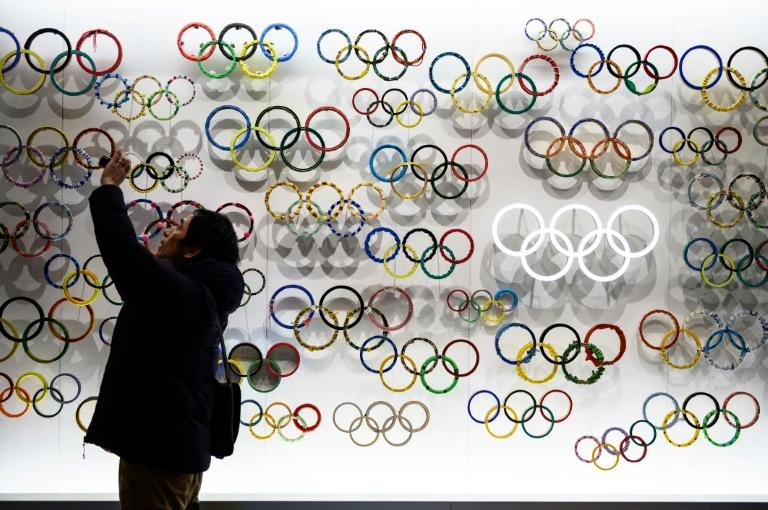 A man takes pictures at the Japan Olympic Museum in Tokyo. Organisers of the summer games insist they will go ahead despite the coronavirus outbreak
