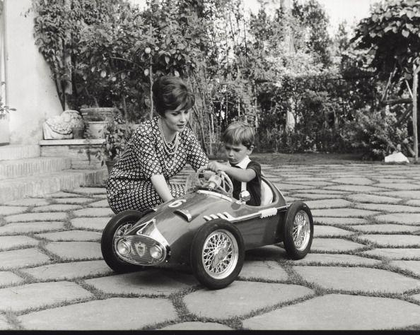 <p>Gina's son Milko Skofic looks ready to race in 1961. The toddler played in a pedal car while the Italian film actress looks on. </p>