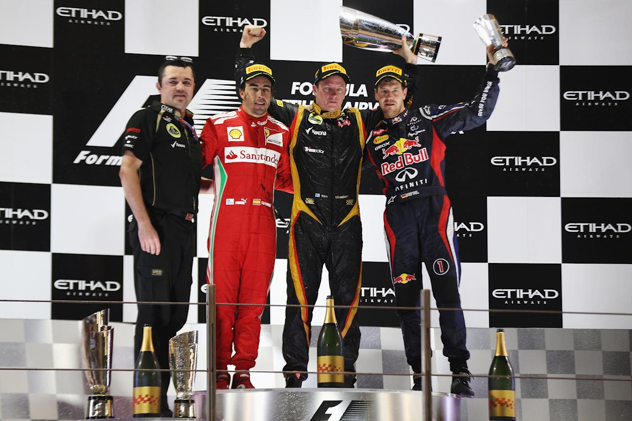 ABU DHABI, UNITED ARAB EMIRATES - NOVEMBER 04:  Race winner Kimi Raikkonen (2nd right) of Finland and Lotus celebrates on the podium with second placed Fernando Alonso (2nd left) of Spain and Ferrari, third placed Sebastian Vettel (right) of Germany and Red Bull Racing and Lotus Team Principal Eric Boullier (left) following the Abu Dhabi Formula One Grand Prix at the Yas Marina Circuit on November 4, 2012 in Abu Dhabi, United Arab Emirates.  (Photo by Mark Thompson/Getty Images)