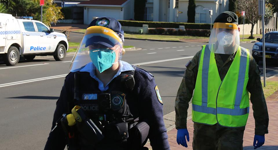 A NSW Police officer and ADF troop wear PPE gear while conducting COVID compliance checks in western Sydney. Source: NSW Police
