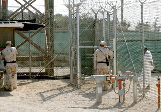GUANTANAMO BAY, CUBA - MAY 09: (IMAGE REVIEWED BY U.S. MILITARY PRIOR TO TRANSMISSION) Two members of the U.S. Military stand near a detainee at Camp 4 inside of Camp Delta May 9, 2006 in Guantanamo Bay, Cuba. Camp Delta was first occupied on April 28, 2002, when 300 detainees previously held at Camp X-Ray were transferred to Camp Delta. The rest of the detainees were moved on April 29. Camp X-Ray closed down on that same day. (Photo by Mark Wilson/Getty Images)
