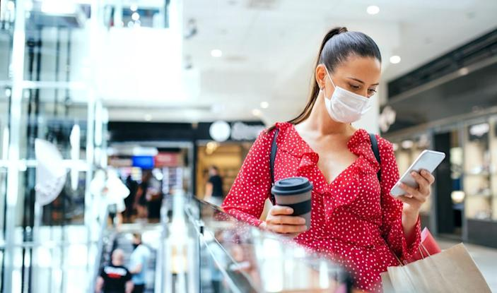 woman wearing a face mask checking her phone in a shopping mall.