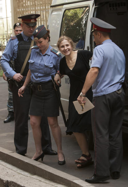 "Maria Alekhina, second right, a member of the feminist punk group Pussy Riot is escorted to a court room in Moscow, Monday, Aug. 6, 2012. Russia's President Vladimir Putin on Thursday criticized the feminist punk rockers facing trial for performing a ""punk prayer"" against him at Moscow's main cathedral, but said that a punishment for them shouldn't be too severe.(AP Photo/Alexander Zemlianichenko)"