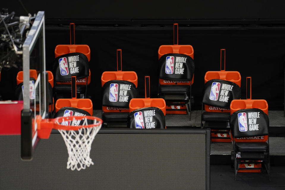 A basketball hoop to the left and socially distanced seats with padding that reads 'a whole new game.'