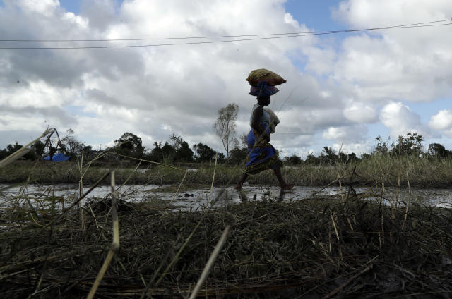 A woman carrying her child walks alongside a collapsed bridge in Nhamatanda, about 100km west of Beira, Thursday, March 21, 2019. Hundreds are dead, many more missing and thousands at risk from massive flooding in Mozambique, Malawi and Zimbabwe caused by Cyclone Idai. A week after Cyclone Idai lashed southern Africa, flooding still raged Thursday as torrential rains caused a dam to overflow in Zimbabwe, threatening riverside populations. The confirmed death toll in Zimbabwe, neighboring Mozambique and Malawi surpassed 500, with hundreds more feared dead in towns and villages that were completely submerged. (AP Photo/Themba Hadebe)
