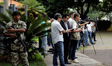 Journalists are seen outside the presidential residence during a meeting of senators, deputies, governors, and local leaders with Paraguay's President Horacio Cartes (not pictured), in Asuncion, Paraguay April 3, 2017. REUTERS/Jorge Adorno