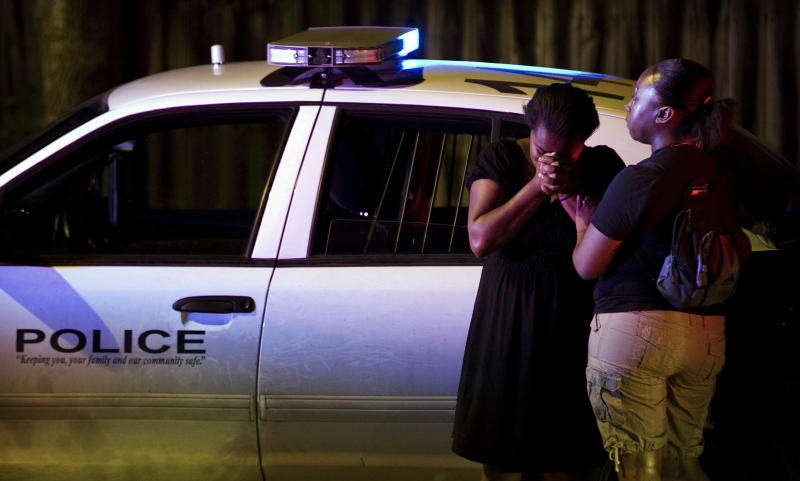 A woman cries at the scene of a police shooting on Thursday April 5, 2012 in Austin, Texas. An Austin police officer fatally shot a man after a traffic stop that authorities said quickly escalated.    (AP Photo/Austin American-Statesman, Jay Janner) MAGS OUT; NO SALES; INTERNET AND TV MUST CREDIT PHOTOGRAPHER AND STATESMAN.COM