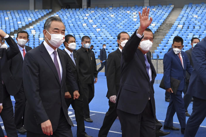 Chinese Foreign Minister Wang Yi front left, accompanies by Cambodian Prime Minister Hun Sen, front right, walks around during a tour to the Morodok Techo National Stadium, as it was handed over to the Cambodian organizing committee of the Southeast Asian Games, in Phnom Penh, Cambodia, Sunday, Sept. 12, 2021. Wang is visiting Cambodia, where he met with Hun Sen and other officials to discuss COVID-19 and other regional issues. (Tang Chhin Sothy/Pool Photo via AP)