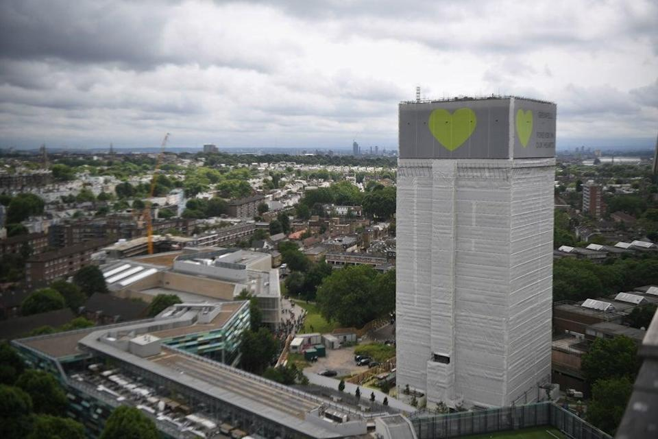 A banner with a green heart is wrapped around the Grenfell Tower one year after the blaze, which claimed 72 lives (Victoria Jones/PA) (PA Archive)