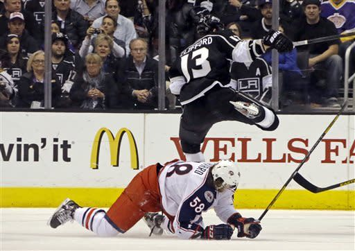 Los Angeles Kings left wing Kyle Clifford (13) flies over Columbus Blue Jackets defenseman David Savard (58) in the first period of an NHL hockey game in Los Angeles, Thursday, April 18, 2013. (AP Photo/Reed Saxon)