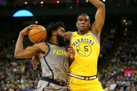 Mar 21, 2019; Oakland, CA, USA; Indiana Pacers guard Tyreke Evans (12) attempts to drive past Golden State Warriors center Kevon Looney (5) in the first quarter at Oracle Arena. Mandatory Credit: Cary Edmondson-USA TODAY Sports