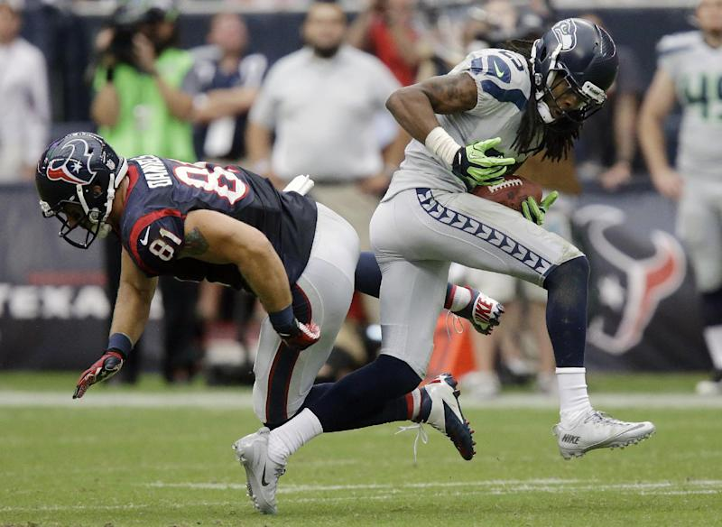 FILE - In this Sept. 29, 2013 file photo, Seattle Seahawks' Richard Sherman (25) intercepts the ball in front of Houston Texans' Owen Daniels (81), and runs for a touchdown, during the fourth quarter an NFL football game in Houston. Players such as Sherman, Tampa Bay's Darrelle Revis and Denver's Champ Bailey have made the lock-down cornerback a must-have accessory in today's NFL. (AP Photo/Patric Schneider, File)