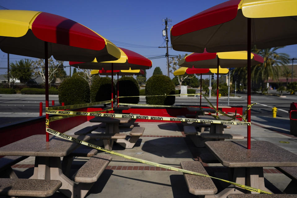 The outdoor dining area of a fast-food restaurant is taped off in Norwalk, Calif., Tuesday, Nov. 24, 2020. Waiters and bartenders are being thrown out of work – again – as governors and local officials shut down indoor dining and drinking establishments to combat the nationwide surge in coronavirus infections that is overwhelming hospitals and dashing hopes for a quick economic recovery.(AP Photo/Jae C. Hong)