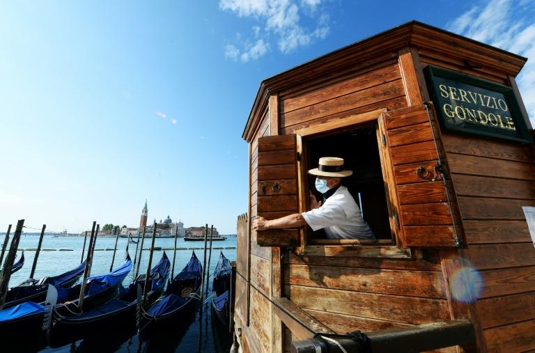 A masked gondolier hopes domestic and foreign tourists will take a punt on Italy this summer with the country facing its deepest recession since World War II (AFP Photo/ANDREA PATTARO)