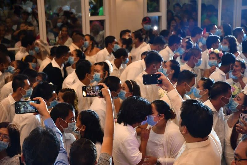 Filipino couples kiss while wearing their face masks in a government-sponsored mass wedding in Bacolod City