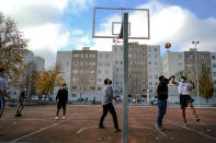 Residents keep a safe distance and wear face masks to prevent the spread of the coronavirus while playing basketball in a neighborhood outside of Pamplona, northern Spain, Friday, Nov. 13, 2020. (AP Photo/Alvaro Barrientos)
