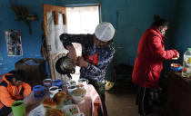 Gracce Kelly Flores, a 12-year-old boxer who goes by the nickname Hands of Stone, fills breakfast cups with boiled water for hot chocolate as she helps prepare breakfast for her family, after her daily boxing workout in Palca, Bolivia, early Thursday, June 10, 2021, amid the COVID-19 pandemic. At age 8, Flores defeated a 10-year-old boy, and with three national boxing medals under her belt, she dreams of reaching the women's boxing world championship. (AP Photo/Juan Karita)