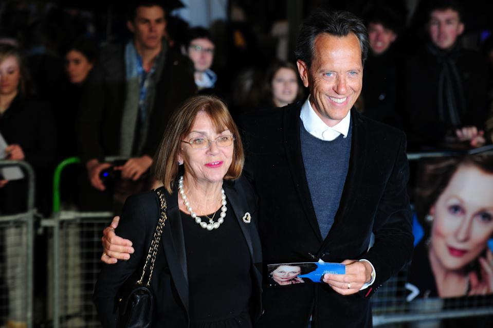 British actor Richard E Grant (R) poses with his wife Joan Washington (L) on the blue carpet as she arrives to attend the European premiere of the film